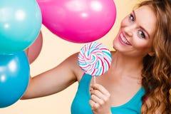 Vrouw met kleurrijke ballons en lolly stock afbeelding