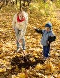 Vrouw met kleuter het plaatsen boom in de herfst Royalty-vrije Stock Foto's