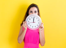 Vrouw met klok die bijna 12 tonen Royalty-vrije Stock Foto