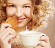 Vrouw met koffie en koekjes stock foto