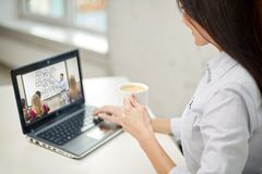Vrouw met koffie letten op webinar op laptop stock afbeeldingen