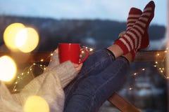 Vrouw met kop hete drank en Kerstmislichten die op balkon rusten De winter royalty-vrije stock afbeelding