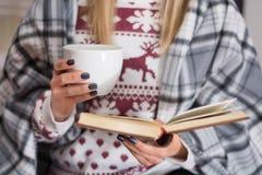 Vrouw met kop thee en lezingsboek in lange de winternacht royalty-vrije stock foto