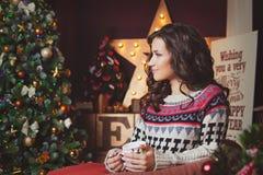 Vrouw met kop van hete drankzitting op bank door verfraaide Kerstboom Royalty-vrije Stock Foto