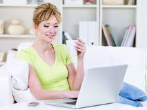 Vrouw met kop van koffie en laptop thuis Royalty-vrije Stock Afbeeldingen
