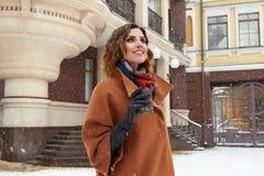 Vrouw met kop van koffiegang op Kerstmisnieuwjaar van de sneeuwstraat royalty-vrije stock afbeeldingen