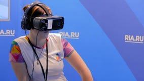 Vrouw met kort haar gebruikend virtuele werkelijkheidshoofdtelefoon en rond kijkend stock videobeelden