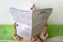 vrouw met krant Het brunette zit op de bank thuis na bad en het lezen stock fotografie