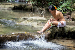 Vrouw met kruikzitting door de kreek stock foto