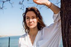 Vrouw met krullend haar die zich in een park bevinden Vrouw in wit overhemd, zonnige dag, gelukkig, aantrekkelijk denken, Stock Fotografie