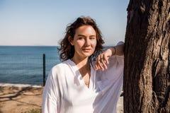 Vrouw met krullend haar die zich in een park bevinden Vrouw in wit overhemd, zonnige dag, gelukkig, aantrekkelijk denken, Stock Afbeeldingen