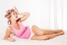 Vrouw met krulspelden in bed Royalty-vrije Stock Foto