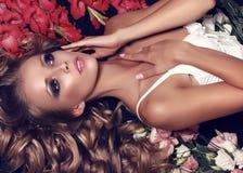 Vrouw met lang blond haar in kantlingerie die onder bloemen liggen Royalty-vrije Stock Fotografie
