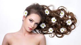 Vrouw met lang haar en camomiles Stock Foto's