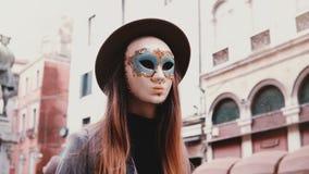 Vrouw met lang haar en hoed die een wit Carnaval-gezichtsmasker in de straat van Venetië, Italië dragen die camera bekijken, die  stock videobeelden