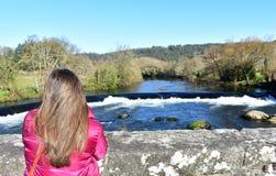 Vrouw met lang haar op een brug die de mening bekijken Rivier, waterval en bos met blauwe hemel Ponte Maceira, Spanje royalty-vrije stock foto's