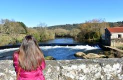 Vrouw met lang haar op een brug die de mening bekijken Rivier, waterval en bos met blauwe hemel Ponte Maceira, Spanje stock fotografie