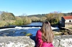 Vrouw met lang haar op een brug die de mening bekijken Rivier, waterval en bos met blauwe hemel Ponte Maceira, Spanje royalty-vrije stock afbeeldingen