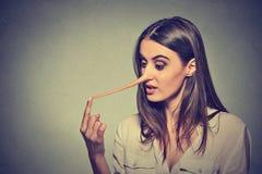Vrouw met lange die neus op grijze muurachtergrond wordt geïsoleerd Leugenaarconcept Stock Fotografie