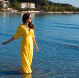 Vrouw met lange gele kleding Stock Afbeeldingen