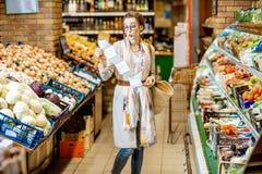Vrouw met lange het winkelen lijst in de supermarkt stock afbeeldingen