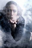 Vrouw met lange krullende haar blazende rook Stock Foto's
