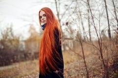 Vrouw met lange rode haargangen in de herfst op de straat Geheimzinnige dromerig ziet en het beeld van het meisje eruit Roodharig stock foto