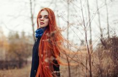 Vrouw met lange rode haargangen in de herfst op de straat Geheimzinnige dromerig ziet en het beeld van het meisje eruit Roodharig stock foto's