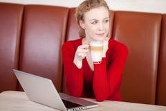 Vrouw met laptop dagdromen in koffiebar stock afbeeldingen