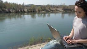 Vrouw met laptop die door de rivier werken Het meisje typt op laptop in de verse lucht stock video
