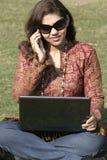 Vrouw met laptop die op mobiele telefoon spreekt stock foto's