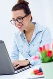 Vrouw met laptop die thuis werken stock afbeeldingen
