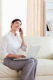 Vrouw met laptop en een telefoon Stock Afbeelding