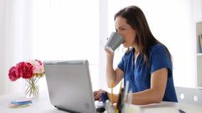 Vrouw met laptop en koffie thuis of bureau stock video