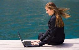 Vrouw met laptop en overzees stock afbeelding