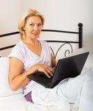Vrouw met laptop het leggen Royalty-vrije Stock Foto's