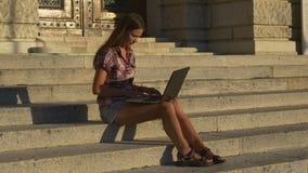 Vrouw met laptop op de oude treden stock footage