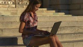 Vrouw met laptop op de stappen van het historische gebouw stock videobeelden