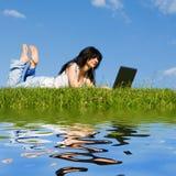 Vrouw met laptop op het groene gras stock foto