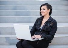 Vrouw met laptop op treden Stock Foto