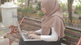 Vrouw met laptop zitting op bank bij park stock videobeelden
