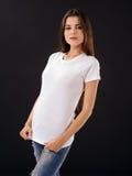 Vrouw met leeg wit overhemd over zwarte achtergrond Stock Afbeelding