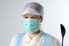 Vrouw met lepel die voor de voedselindustrie werkt stock afbeelding