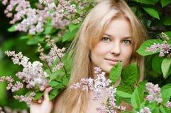 Vrouw met lilac bloem op gezicht stock foto