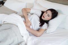 Vrouw met maagpijn op bed royalty-vrije stock fotografie