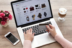 Vrouw met MacBook en de winkelende eBay dienst van iPhoneinternet Stock Foto's