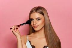 Vrouw met make-upborstel stock afbeeldingen