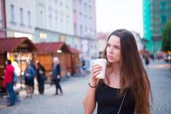 Vrouw met meeneemdrankgang op straat Beschikbare de koffiekop van de vrouwengreep Koffie of theestemming Drank en voedsel tijdens stock fotografie
