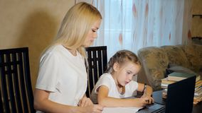 Vrouw met meisje die thuiswerk samen doen stock fotografie