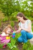 Vrouw met meisje het water geven bloemen royalty-vrije stock foto's